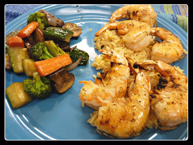Grilled shrimp served up on a bed of rice pilaf with a side of veggies.